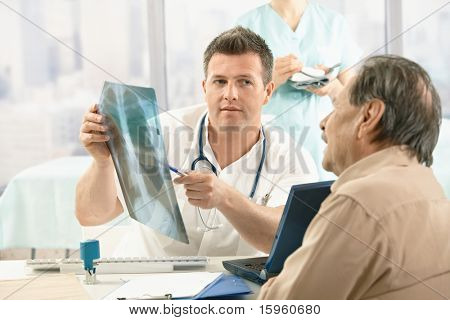 Doctor showing diagnosis of x-ray image to older patient sitting at office desk.?