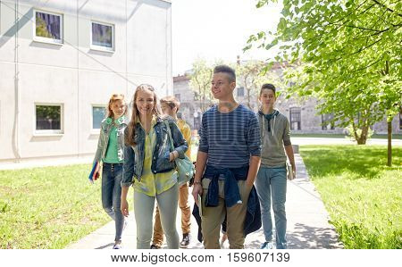 education, high school, communication and people concept - group of happy teenage students walking outdoors