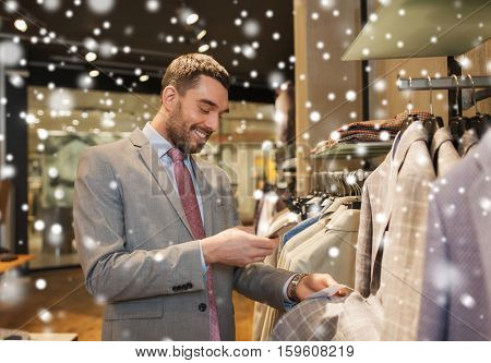 sale, shopping, fashion, technology and people concept - happy man or businessman in suit with smartphone choosing clothes at clothing store over snow
