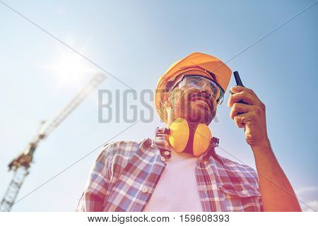 industry, building, technology and people concept - male builder in hardhat with walkie talkie or radio outdoors
