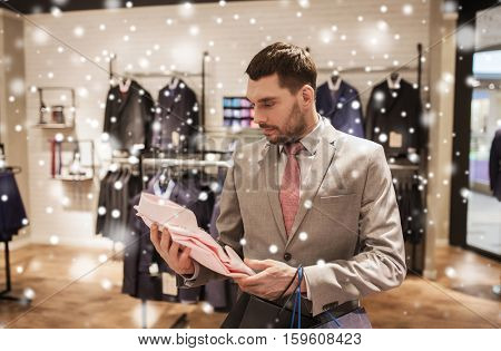 sale, fashion, style and people concept - elegant young man or businessman in suit with shopping bags choosing shirt in mall or clothing store over snow