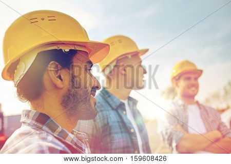business, building, teamwork and people concept - group of smiling builders in hardhats at construction site