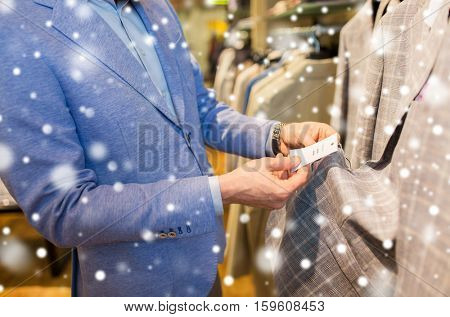 sale, shopping, fashion, style and people concept - close up of elegant young man in jacket choosing clothes and looking at price tag in mall or clothing store over snow