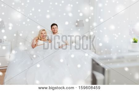 people, rest, love, television and entertainment concept - happy smiling couple lying in bed and watching tv at home over snow