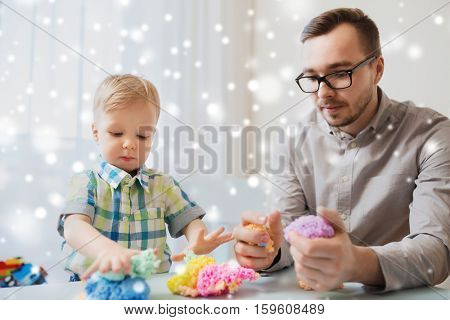family, childhood, creativity, activity and people concept - happy father and little son playing with ball clay at home over snow