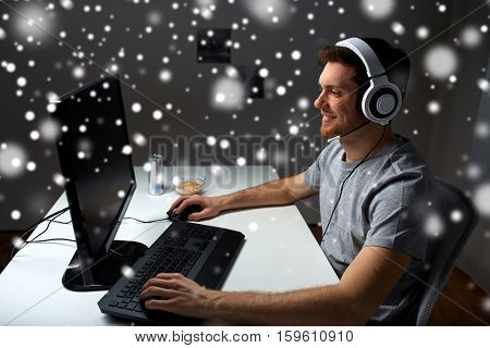 technology, gaming, entertainment, let's play and people concept - happy young man in headset with pc computer playing game at home and streaming playthrough or walkthrough video over snow