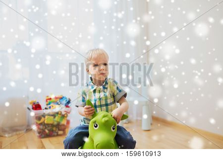 childhood, toys and people concept - happy little baby boy playing with ride-on toy horse at home over snow