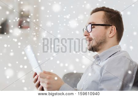 technology, people and distance learning concept - happy man working with tablet pc computer at home over snow