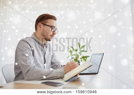business, startup and people concept - businessman or creative male worker writing to notebook or diary with pen at home office over snow