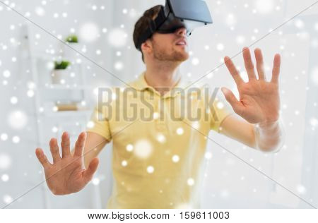 technology, augmented reality, winter, christmas and people concept - close up of happy young man with virtual headset or 3d glasses playing videogame at home over snow