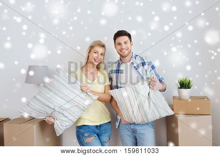 home, people, repair and real estate concept - smiling couple with big cardboard boxes, pillows and other stuff moving to new place over snow