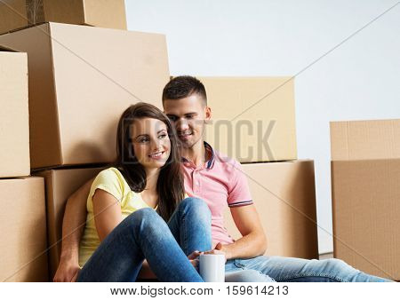 Young couple moving in a new home. Man and woman with boxes.