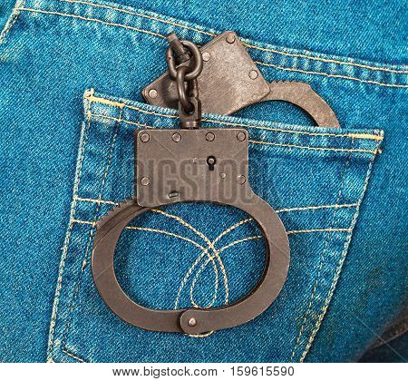 Police steel handcuffs in back jeans pocket