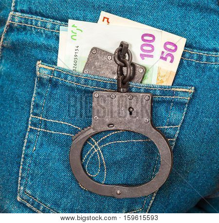 Police black metal handcuffs and euro currency in back jeans pocket