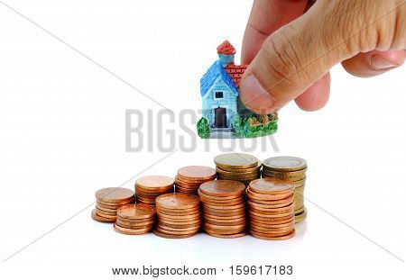 Collect coins for buy a house concept with model home in the hands.