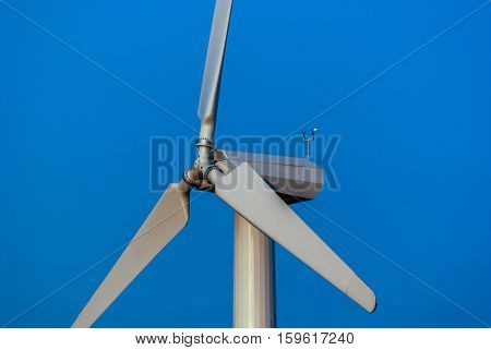 White wind turbine with blue sky in the background