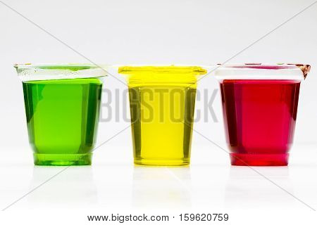 Sweet colored jelly in jars close-up on a white background.