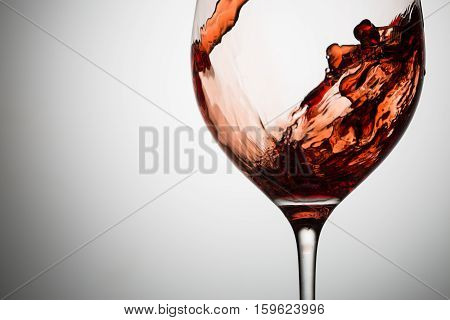 Beautiful waves of red wine in glass closeup. Image with space for text