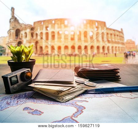 passport euro money bank note and action camera on wood table against colosseum scene background for rome italy traveling theme