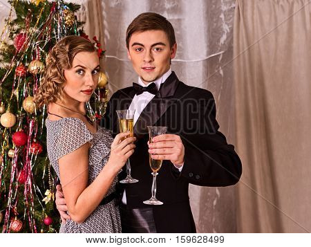 Couple on party near Christmas tree. Christmas date loving couple at home. Man hugging woman waist. Christmas tree on background. Retro style.