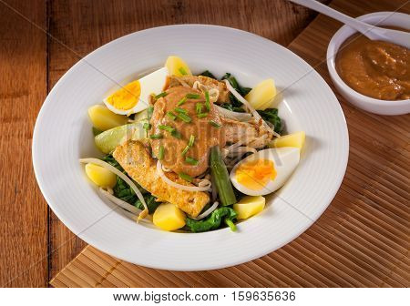 Gado-gado Indonesian salad served with peanut sauce. Ingredients: tofu spinach string beans soy sprouts potatoes cucumber and boiled eggs.