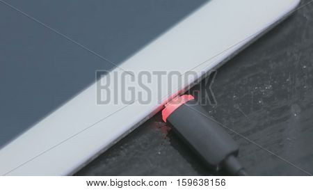 Pc digital tablet with black lightning charging cable - USB data cable connecting on modern gadget. Close up
