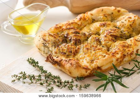 Italian focaccia bread with oregano olive oil and rosemary on a cutting board.