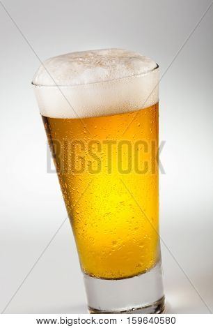 Ice cold glass of beer with foam and condensation drops