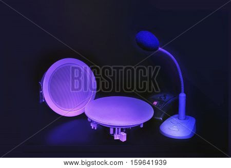 Black microphone and small white loudspeakers in a dark blue tones