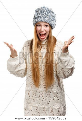 Young expressive beautiful stylish blonde woman in white patterned sweater and grey funny knitted hat shouts and gestures with her arms spread isolated on white background.