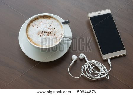 hot coffee in white cup white foam and mobile phone and headphones with silver spoon on wooden table at coffee time sunset / hot coffee mobile phone
