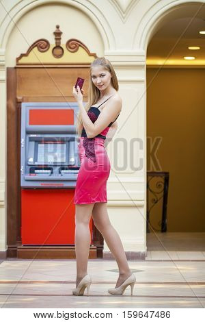 Young happy blonde woman in red dress withdrawing money from credit card at ATM