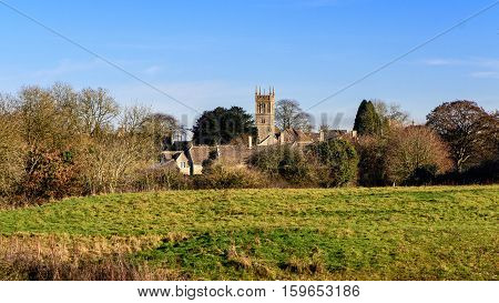 Colerne with Church of St. John the Baptist, Wiltshire. Parish church within a rural English landscape with fields in front of blue clear winter sky