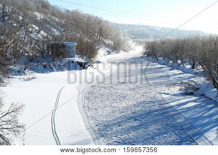Frozen river. Snowcapped landscape. Snowcapped mountain. Trees. Traces on snow.