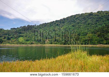 Beautiful landscape of the Laguna Verde with a boat in Apaneca Ruta de Las Flores itinerary El Salvador Central America.