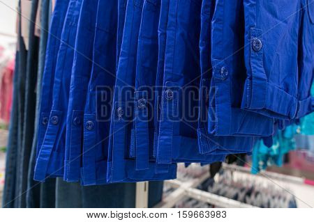 Shirts on hangers. Clothes in blue tones. Blue shirts. Blue color. Clothes in blue tones.