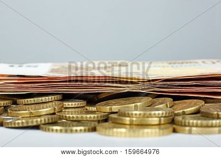 Euro banknotes and coins on white table.