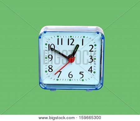 Table clock square shape showing one o'clock isolated on green background closeup