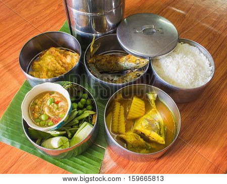 Thai food in food carrier thai styeomeletdeepfried fishYellow Curry with Fish chili saurcevegetablerice.thai lauch jar.thai tiffin.