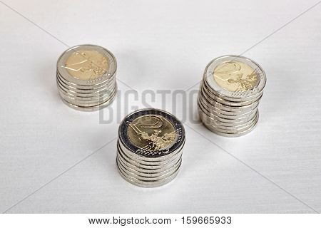 Euro coins stacks close up on white table.
