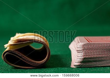 Poker cards and roll of money on green table.Ιllegal gambling.