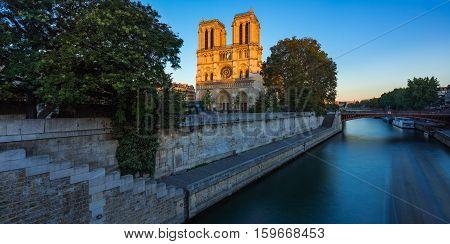 Notre Dame de Paris cathedral on Ile de La Cite at sunset with the Seine River. Summer evening in Paris France