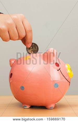 Kid's hand put a coin in a pink pig bank.