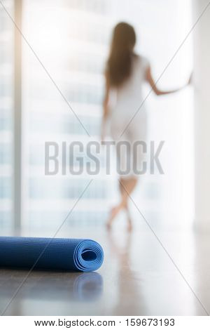 Young woman in a modern studio, resting after yoga, fitness class, standing near the floor window, looking out. Yoga accessories, focus on the mat, white full height windows. Healthy lifestyle concept