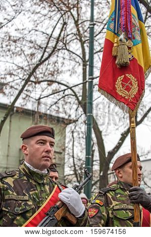 TIMISOARA ROMANIA - DECEMBER 1 2016: Military parade at Romanian National Day. Soldiers in formation with flag. Picture is taken in front of the Administrative Palace in Timisoara.