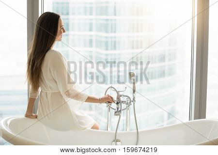 Profile portrait of a young woman in a gown sitting at the side of freestanding white tub, favorite bathing rituals, healing bath, hydrotherapy, trying to reduce overall tension in the body and mind