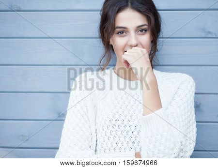 Beautiful natural young smiling shy friendly brunette woman wearing knitted sweater on a grey wooden background.