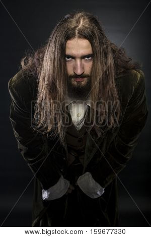 studio portrait of a pirate leaning towards the viewer on black background