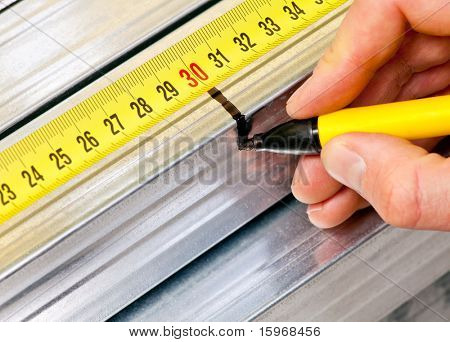 Hand holding marker pen marking measurement on a metal stud