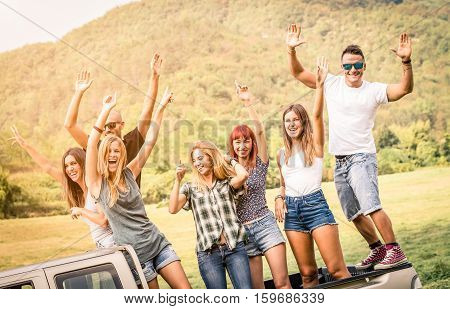 Group of happy friends having fun at countryside party ride on pick up truck car - Friendship concept with young people sharing time together on farmhouse picnic - Soft warm desaturated green filter